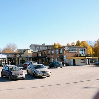 На фото: асфальтированная территория стоянки автотранспорта перед торговым центром, двухэтажное здание торгового центра с пристройкой, за ним на дальнем плане - жилые дома, справа - сквер с деревьями