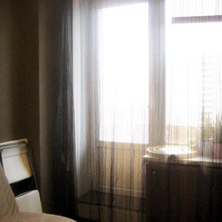 На фото: часть помещения жилой комнаты, одно с балконной дверью, слева от окна - складной стул у стены, мягкий диван или кресло
