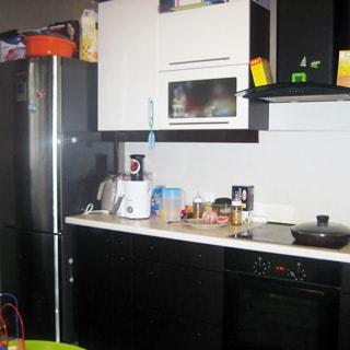 На фото: часть помещения кухни. Слева-направо: большой двухкамерный холодильник, тумба-стол и электрическая плита с духовым шкафом с общей столешницей, над тумбой - навесной кухонный шкаф, над плитой - вытяжка