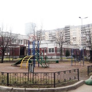 На фото: часть придомовой дворовой территории, газон с ограждением, оборудованная детская площадка, за ней - детский сад, огороженный забором
