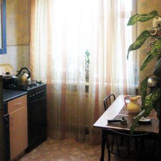 На фото: часть помещения кухни, большое окно, слева от окна - 4-комфорочная газовая плита с духовкой, кухонная тумба-стол, под окном - радиатор центрального отопления, справа от окна - обеденный стол, два стула у стола, полы - линолеум