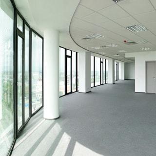 На фото: светлый просторный холл офисного помещения, слева сполшное остекление от пола до потолка, потолки навесные с встроенными светильниками, полы - ковролин серого цвета