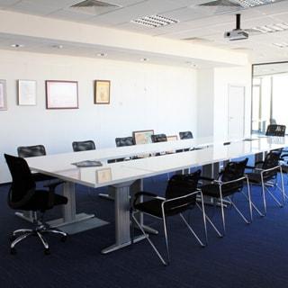 На фото: часть офисного помещения для проведения совещаний, большой прямоугольный стол, офисные стулья и кресло руководителя, потолки - навесные с встроенными светильниками, на потолке установлен проектор, полы - ковролин синего цвета