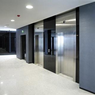 На фото: лифтовый холл, два лифта, выход на пожарную лестницу, на потолке - датчик пожарной сигнализации, встроенные светильники