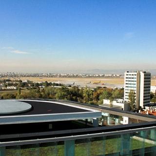 На фото: вид с высоты здания бизнес-центра на городские кварталы и аэропорт, городские постройки, сооружения и площадки аэродрома, самолеты на стоянках