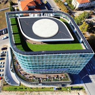 На фото: вид на здание сверху, видна вся кровля последнего этажа, газон, стеклянное ограждение полной высоты по всему периметру, в центре  - вертолетная площадка, за ней элементы системы кондиционирования и вентиляции