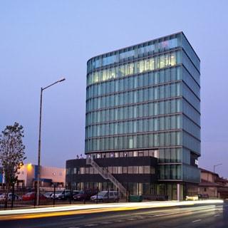 На фото: фасад 9-этажного офисного здания в вечернее время, полное остекление фасада, галерея на втором и третьем этажах, перед зданием с левой стороны - огороженная площадка для парковки автомобилей, с правой стороны - тротуар и проезжая часть автодороги