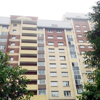 На фото: часть фасада многоэтажного дома с застекленными лоджиями