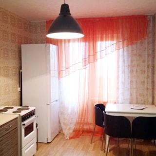 На фото: кухня, окно и выход на лоджию, плита - электрическая, двухкамерный холодильник, кухонный стол-тумба, обеденный стол со стульями, стены оклеены обоями, пол - ламинат