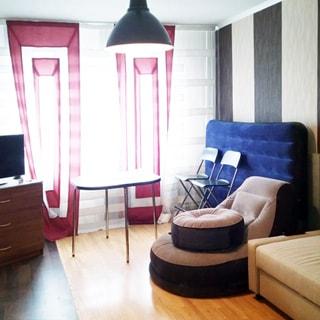 На фото: светлая комната с окном, диван, кресло, комод, на комоде - телевизор, стены оклеены обоями, пол - ламинат