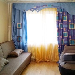 На фото: комната с окном, диван, кресло, стены оклеены обоями, пол - ламинат