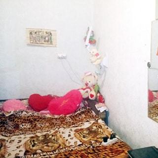 На фото: часть помещения жилой комнаты, прямо у стены диван-кровать в разложенном состоянии застелен пледом, справа на стене - лампа для чтения, зеркала, стены оклеены светлыми обоями
