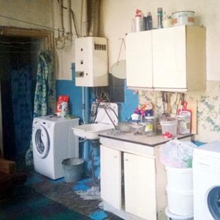 На фото: часть помещения кухни, слева - вход в кухню, справа от входа вдоль стены: стиральная машина, эмалированная раковина, над ней - газовая колонка, справа от раковины - тумба-стол, над ней - навесная кухонная полка закрытого типа, правее - еще одна стиральная машина