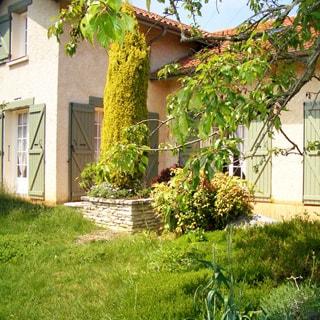 На фото: часть фасада загородного одноэтажного дома с мансардой, застекленные верандные двери с деревянными ставнями, кровля - черепица, перед домом - газон, садовые посадки