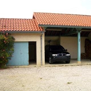 На фото: гараж на две легковые автомашины, слева пристройка со сдвижной дверью, кровля - черепица, дворовая территория перед гаражом отсыпана гравием