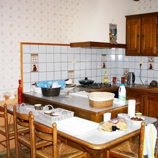 На фото: часть помещения кухни, на переднем плане - обеденный стол со стульями, на заднем плане - кухонная рабочая поверхность с варочной газовой панелью, вытяжкой, со встроенной кухонной мебелью, навесными шкафами, кухонный фартук облицован плиткой