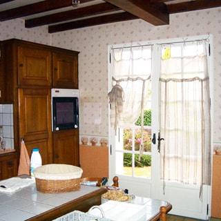 На фото: часть помещения кухни, на переднем плане - обеденный стол со стульями, на заднем плане - встроенная кухонная мебель, встроенный духовой шкаф, застекленная верандная дверь с выходом на террасу