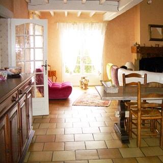 На фото: часть помещения гостиной с выходом в кухню и на террасу, слева - комод, у выхода на террасу - мягкое кресло, справа - стол со стульями, на дальнем плане - камин, мягкие кресла, полы - плитка