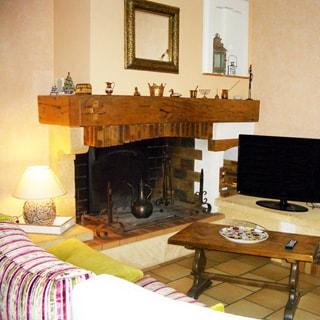 На фото: часть помещения гостиной, камин, у камина - журнальный столик, телевизор, мягкая мебель, полы - плитка