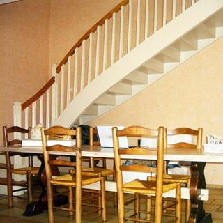 На фото: часть помещения гостиной, стол со стульями, лестница на второй этаж, полы - плитка