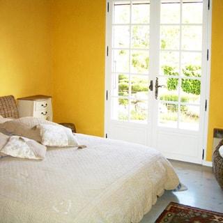 На фото: часть помещения спальни, двуспальная кровать, прикроватная тумбочка, верендная дверь с выходом в сад