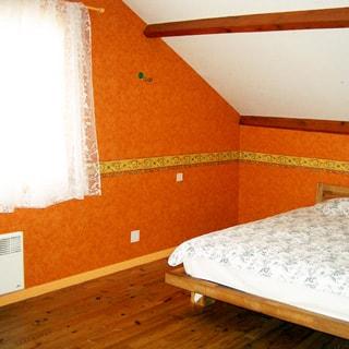 На фото: часть помещения мансардного этажа, двуспальная кровать, окно, полы - дощатые