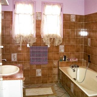 На фото: часть помещения ванной с двумя окнами, слева умывальник, справа - ванная со смесителем, полы и стены - плитка