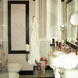 На фото: часть помещения совмещенного санузла, справа умывальник с большой рабочей поверхностью и зеркалом во всю стену, слева - унитаз, биде