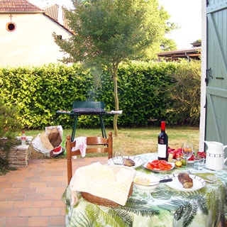На фото: мощеная плиткой терраса с накрытым обеденным столом, на заднем плане - дымящийся мангал, газон, живая изгородь из кустов