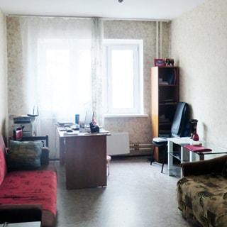 На фото: часть помещения жилой комнаты, большое трехстворчатое окно, у окна - письменный стол, слеву у стены - диван, справа у стены - книжный шкаф, журнальный столик, диван, полы - линолеум