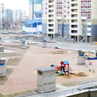 На фото: вид из окна во двор, на кровле подземного паркинга - детская площадка, газоны, вентиляционные выходы, территория огорожена металлическим ограждением