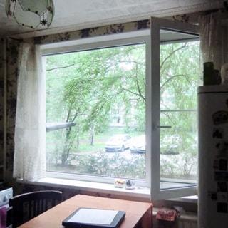 На фото: часть помещения кухни, открытое большое трехстворчатое окно во двор, слева от окна - газовая плита, у окна - стол со стулом, справа от окна - холодильник, под окном - радиатор центрального отопления, на потолке - люстра