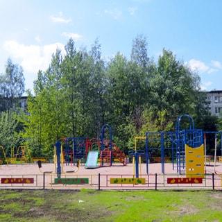 На фото: оборудованная детская площадка с горками, турникетами, лесенками и качелями, огорожена, вокруг площадки - газон, деревья, за деревьями на заднем плане - панельный жилой дом