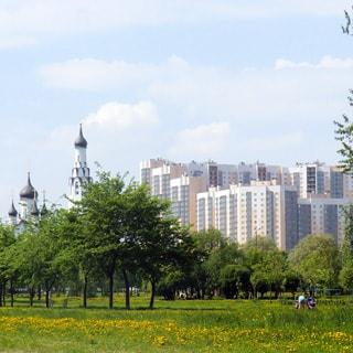 На фото: территория парка или сквера, газоны, деревья, на дальнем плане - православный храм, еще дальше - многоэтажные жилые дома