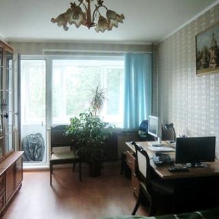 На фото: часть помещения жилой комнаты, большое окно, балконная дверь открыта, слева у стены - шкаф, справа у стены - письменный стол, стул, стены оклеены обоями, полы - ламинат, на потолке - люстра