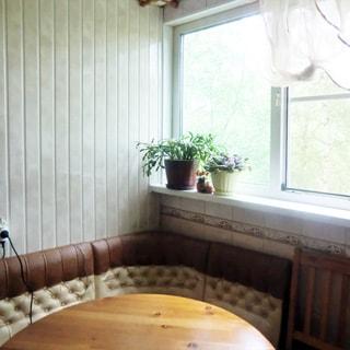 На фото: часть помещения кухни, окно с высоким подоконником, у окна - мягкий уголок и обеденный стол, стены облицованы плиткой