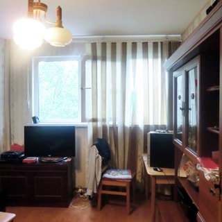 На фото: часть помещения жилой комнаты, большое трехстворчатое окно, высокий подоконник, слева у окна - тумба, на тумбе - телевизор, справа у стены - письменный стол, стул, сервант, полы - ламинат, на потолке - люстра