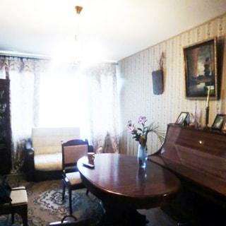 На фото: часть помещения жилой комнаты, большое трехстворчатое окно, высокий подоконник, у окна - мягкий диван, в центре комнаты - обеденный стол, стул, справа у стены - пианино, стены оклеены обоями, полы - ламинат, на потолке - люстра