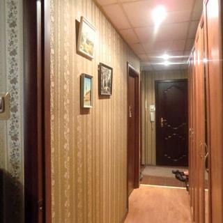 На фото: часть помещения прихожей и коридора, стены оклеены обоями, металлическая входная дверь, полы в коридоре - ламинат, в прихожей - плитка, на потолке - точечные светильники