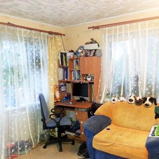 На фото: часть помещения жилой комнаты, комната угловая, два окна, между окнами в углу - компьютерный стол-стеллаж, офисное кресло, справа - мягкий диван