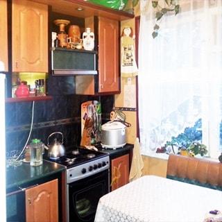 На фото: часть помещения кухни, окно, слева от окна вдоль стены встроенная кухонная мебель, 4-комфорочная газовая плита с духовкой, вытяжка, справа у окна - обеденный стол