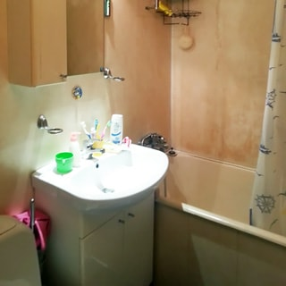 На фото: часть помещения санузла, керамическая раковина со смесителем на тумбе, на раковиной - навесной шкафчик с зеркалом, справа - ванная со смесителем