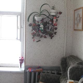 На фото: часть помещения жилой комнаты, окно, справа от окна на уровне подоконника - радиатор центрального отопления, в углу - мягкое кресло, на стене цветы в горшках, эстамп, стены оклеены обоями