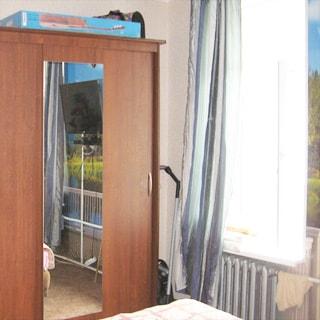 На фото: часть помещения жилой комнаты, окно, под окном - радиатор центрального отопления, слева от окна - платяной шкаф-купе, стены оклеены обоями