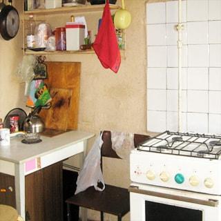 На фото: часть помещения кухни, газовая 4-комфорочная плита с духовкой, часть стены у плиты облицована белой керамической плиткой, слева от плиты - стул, кухонный столик, над ним - кухонные полки