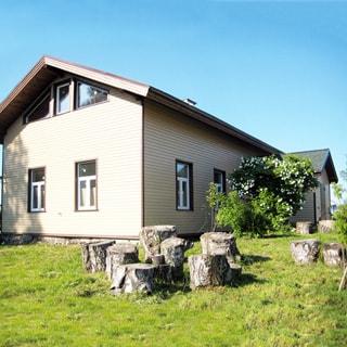 На фото со стороны участка: торцевая и боковая часть фасада одноэтажного дома со скатной кровлей, входная группа, газон перед домом