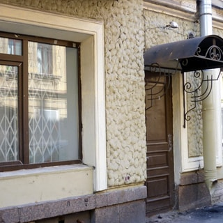 На фото: часть цокольного этажа фасада здания, витринное окно с установленной изнутри защитной решеткой, вход на уровне тротуара с металлической дверью и металлическим козырьком от дождя