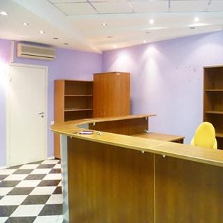 На фото: внутреннее помещение, подвесные потолки с точечными свтильниками, полы - плитка, дверь, над дверью на стене установлен кондиционер, офисная мебель - стойка администратора, три шкафа, стул