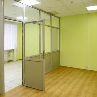 На фото: два внутренних помещения, разделенных офисной светопрозрачной перегородкой полной высоты с дверью, потолки подвесные, полы - линолеум и плитка, потолочные светильники офисного типа, в одном из помещений - окно
