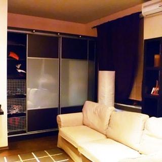 На фото: внутреннее помещение с окном, встроенный шкаф-купе, диван, на стене рядом с окном под потолком установлен кондиционер
